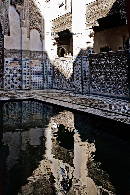 Fes: el Attarine Medersa: reflecting pool in the inner courtyard, looking toward one corner highighted by a sharp noonday sun.