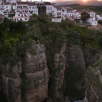 """At break of day: View from the Puente Nuevo (""""new bridge"""", finished 1793) on a line of houses that live on the cliff of El Tajo canyon, 390ft above the Guadalevin River on it's floor."""