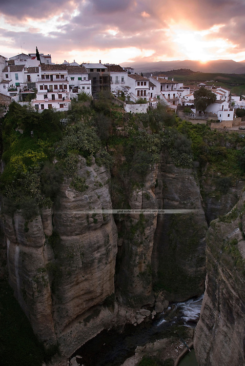 "At break of day: View from the Puente Nuevo (""new bridge"", finished 1793) on a line of houses that live on the cliff of El Tajo canyon, 390ft above the Guadalevin River on it's floor."