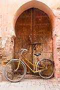 MARRAKESH, MOROCCO - 19TH APRIL 2016 - Bicycle parked up against an old, arched doorway and wall exterior in the old Marrakesh Medina, Morocco.
