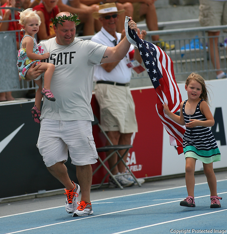 NELSON - 13USA, Des Moines, Ia.- After nine years Adam Nelson got to finally take a victory lap for his win in the 2004 Olympic shot put, which was denied him by another athlete who cheated.    Photo by David Peterson