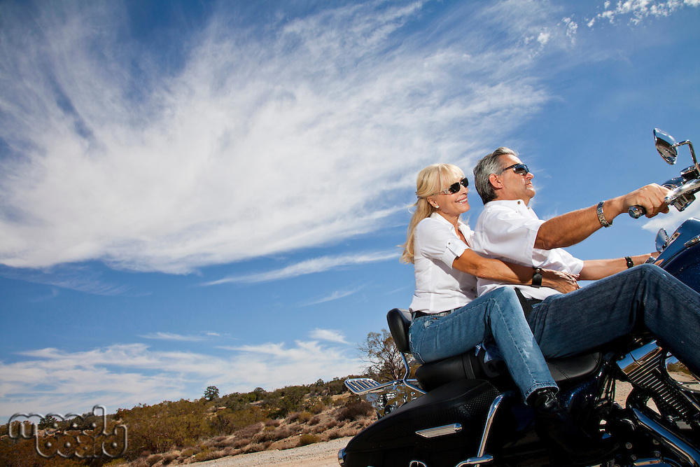 Senior couple riding motorcycle on desert road