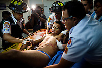 "Paramedics carry a shooting victim onto a gurney at Roosevelt Hospital in Guatemala City, on Saturday, May 5, 2012. The victim, a truck driver, who police nicknamed ""dos equis"", or XX (without name) because he carried no identification, was shot down by police when he did not stop at a checkpoint."