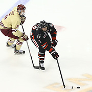 Josh Manson #3 of the Northeastern Huskies keeps the puck form Steven Santini #6 of the Boston College Eagles during The Beanpot Championship Game at TD Garden on February 10, 2014 in Boston, Massachusetts. (Photo by Elan Kawesch)