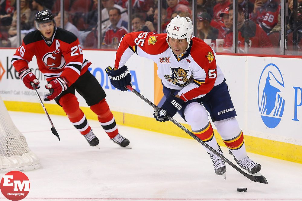 Mar 31, 2014; Newark, NJ, USA; Florida Panthers defenseman Ed Jovanovski (55) skates with the puck while being pursued by New Jersey Devils left wing Patrik Elias (26) during the first period at Prudential Center.