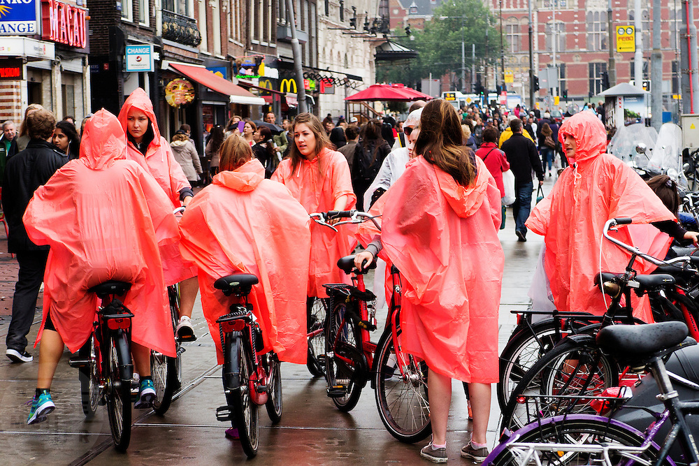 In Amsterdam staan toeristen in de stromende regen met de huurfietsen op het Damrak.<br /> <br /> In Amsterdam tourists wait in the pouring rain with their bikes at the Damrak.