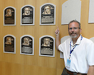 COOPERSTOWN, NY - JULY 28:  Photographer Ron Vesely poses next to the plaque of 2014 Hall of Fame inductee Frank Thomas, on display at the Baseball Hall of Fame and Museum in Cooperstown, New York on July 28 2014.