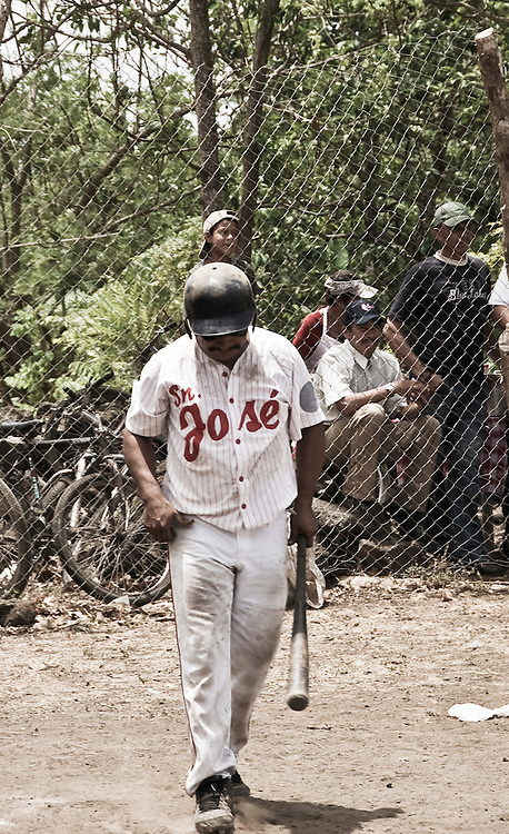 A player steps up to the plate at a local baseball league on Ometepe Island in the middle of Lake Cocibolca, Nicaragua. Baseball is the national sport of Nicaragua. The players and fans are extremely passionate even in these rural leagues playing on dirt fields with antiquated equipment.