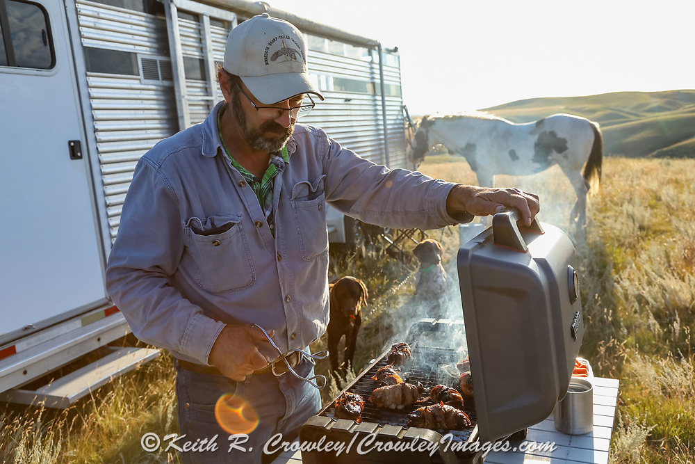 John Zeman grills sharptailed grouse breasts during a Montana prairie grouse hunt.
