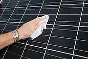 Close-up of a man cleaning a photovoltaic solar energy panel. This panel, or module, is made up of photovoltaic (PV) cells. PV cells convert sunlight into electrical energy. Photovoltaic panels are an economical, efficient way to produce electricity.