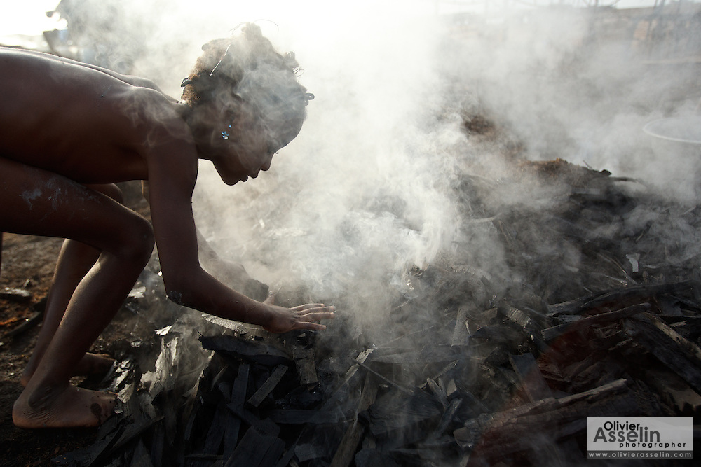 A girl stirs hot charcoal with her bare hands at a wood charcoal production site on the outskirts of San Pedro, Bas-Sassandra region, Côte d'Ivoire on Sunday March 4, 2012. Men, women and children - who don't go to school - work here seven days a week.