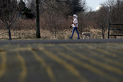 Dog-walker at Warminster community park, located at the former Naval Air Warfare Center Warminster, in Bucks County, Pennsylvania, USA  on February 6, 2019. The United States Environmental Protection Agency (EPA) is expected to release updates on tests of per- and polyfuoroalkyl substances or PFAs pollution in public water supplies for 16 million Americans in 33 states, including Pennsylvania. The federal report is delayed due to January 2019 shutdown. Reps. Brian Fitzpatrick, Republican of Bucks County in Eastern Pennsylvania and Democrat Dan Kildee, of Michigan cochair a bipartisan task force in the House of Representatives, formed to take on the growing PFAS Contamination Crisis. The usage of foam at nearby former military bases is linked to tainted drinking water, affecting tens of thousands of residents in Bucks and Montgomery Counties in Eastern Pennsylvania.