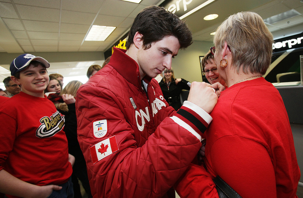 London, Ontario ---02/03/10--- Olympic Gold Medalist in Ice dance Scott Moir signs autographs as he and partner Tessa Virtue are welcomed home by fans and family at the airport in London, Ontario, March 2, 2010.<br /> CP PHOTO/'GEOFF ROBINS