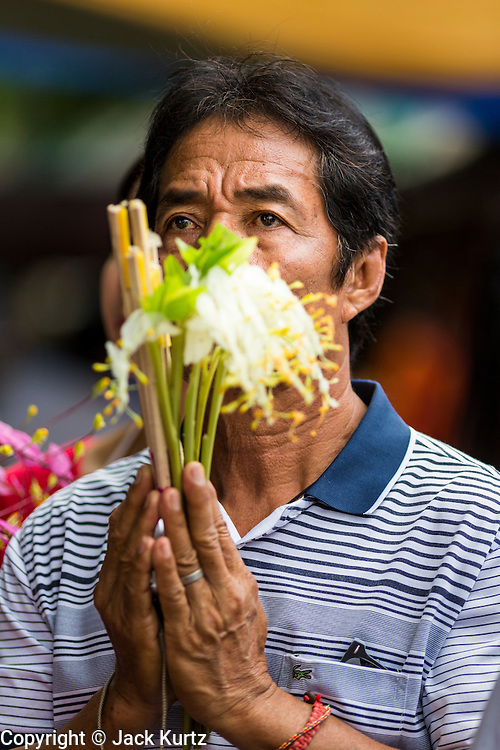 """22 JULY 2013 - PHRA PHUTTHABAT, THAILAND: A man prays during the Tak Bat Dok Mai at Wat Phra Phutthabat in Saraburi province of Thailand, Monday, July 22. Wat Phra Phutthabat is famous for the way it marks the beginning of Vassa, the three-month annual retreat observed by Theravada monks and nuns. The temple is highly revered in Thailand because it houses a footstep of the Buddha. On the first day of Vassa (or Buddhist Lent) people come to the temple to """"make merit"""" and present the monks there with dancing lady ginger flowers, which only bloom in the weeks leading up Vassa. They also present monks with candles and wash their feet. During Vassa, monks and nuns remain inside monasteries and temple grounds, devoting their time to intensive meditation and study. Laypeople support the monastic sangha by bringing food, candles and other offerings to temples. Laypeople also often observe Vassa by giving up something, such as smoking or eating meat. For this reason, westerners sometimes call Vassa the """"Buddhist Lent.""""     PHOTO BY JACK KURTZ"""