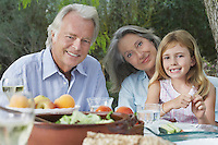 Grandparents with granddaughter (5-6) sitting at garden table portrait