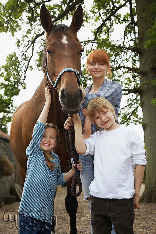 Mother and children (5-6 7-9) with horse outdoors portrait