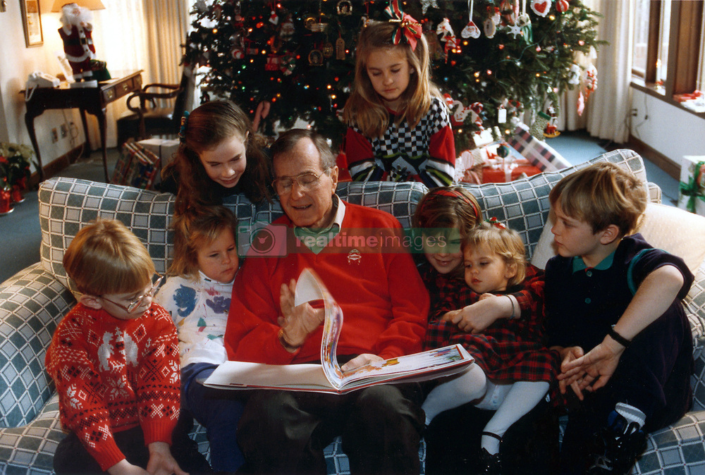 Dec. 24, 1991 - Camp David, Maryland, United States of America - Camp David, Maryland - December 24, 1991 -- United States President George H.W. Bush reads a Christmas story to his grandchildren, Pierce Bush, Marshall Bush, Barbara Bush (daughter of George W. Bush), Lauren Bush, Jenna Bush (daughter of George W. Bush), Ashley Bush and Sam LeBlonde at Camp David in Maryland on Christmas Eve, December 24, 1991..Credit: White House via CNP (Credit Image: © White House/CNP/ZUMAPRESS.com)