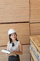 Young female industrial worker inspecting wooden planks