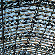 Detail of the distinctive iron and glass arched cover over the platforms of St Pancras Railway Station (now known as St Pancras International). The renovated station features distinctive Victorian architecture and serves as a Eurostar terminal for high-speed trains to Europe. There are also platforms for domestic train services. The distinctive train shed roof was designed by William Henry Barlow.