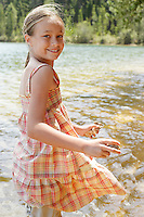 Girl (7-9) standing by lake holding stones portrait.