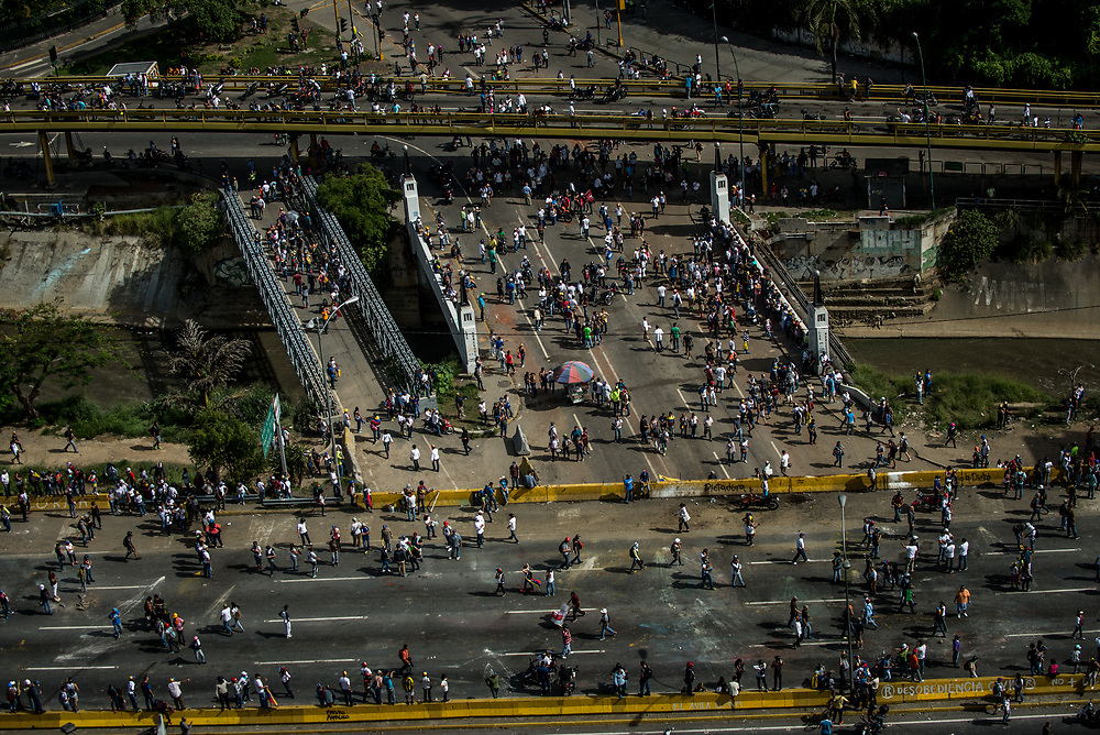 CARACAS, VENEZUELA - MAY 27, 2017:  Anti-government protesters take control of the Francisco Fajardo highway. The streets of Caracas and other cities across Venezuela have been filled with tens of thousands of demonstrators for nearly 100 days of massive protests, held since April 1st. Protesters are enraged at the government for becoming an increasingly repressive, authoritarian regime that has delayed elections, used armed government loyalist to threaten dissidents, called for the Constitution to be re-written to favor them, jailed and tortured protesters and members of the political opposition, and whose corruption and failed economic policy has caused the current economic crisis that has led to widespread food and medicine shortages across the country.  Independent local media report nearly 100 people have been killed during protests and protest-related riots and looting.  The government currently only officially reports 75 deaths.  Over 2,000 people have been injured, and over 3,000 protesters have been detained by authorities.  PHOTO: Meridith Kohut