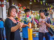 "12 OCTOBER 2012 - RAI KHRING, NAKHON PATHOM, THAILAND:   Thai Buddhists light candles to make merit at Wat Rai Khring in Nakhon Pathom province.  Wat Rai Khring was built in 1791. The Abbot at the time, Somdej Phra Phuttha Chan (Pook), named the temple after the district. When construction was completed, the Buddha image was brought from another temple and enshrined here. Later locals named the image ""Luang Pho Wat Rai Khing"". The Buddha image is of Chiang Saen style and is assumed to have been built by Lanna Thai and Lan Chang craftsmen.     PHOTO BY JACK KURTZ"