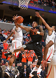Miami (FL) guard Jack McClinton (33) makes a layup past Virginia guard Calvin Baker (4).  The Virginia Cavaliers fell to the Miami Hurricanes 62-55 at the John Paul Jones Arena on the Grounds of the University of Virginia in Charlottesville, VA on February 26, 2009.