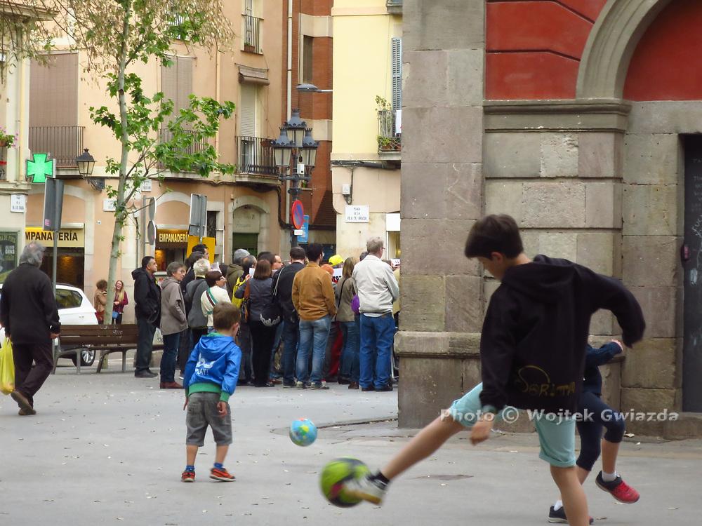 Children playing, adults at Catalan political meeting, Plaça Villa de Gràcia, Barcelona