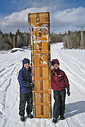 Ashlyn (age 11) and Bryce (age 9) recover after a blazing tobaggan run down the snow covered hill on Vose Mountain, Kingfield, Maine