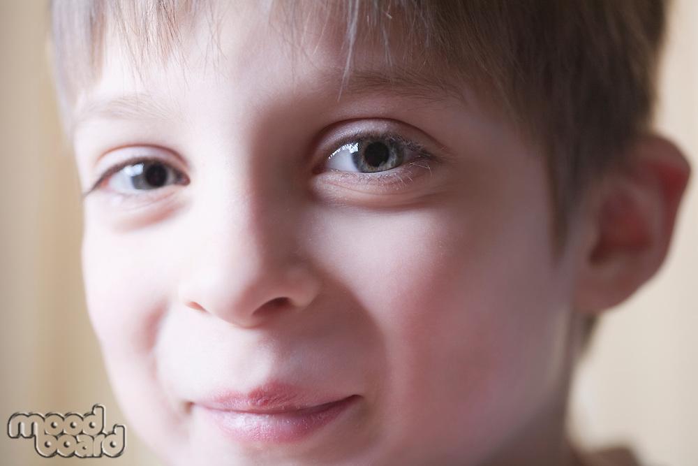 Boy sits smiling at camera