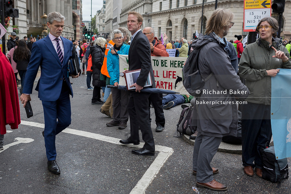 Businessmen and financiers look at environmental activists protesting about Climate Change during the blockade outside the Bank of England in the heart of the capital's financial district, the City of London aka the Square Mile, on the seventh day of a two-week prolonged worldwide protest by members of Extinction Rebellion, on 14th October 2019, in London, England.