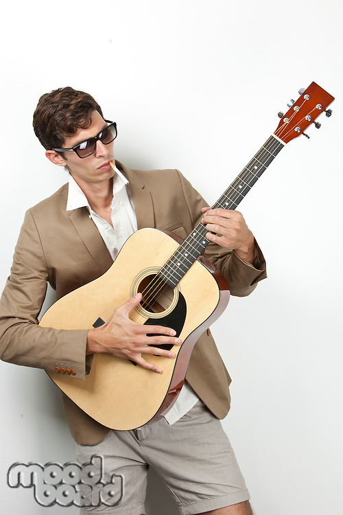Young man smoking while playing guitar against white background