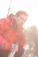 Male hiker having coffee in forest