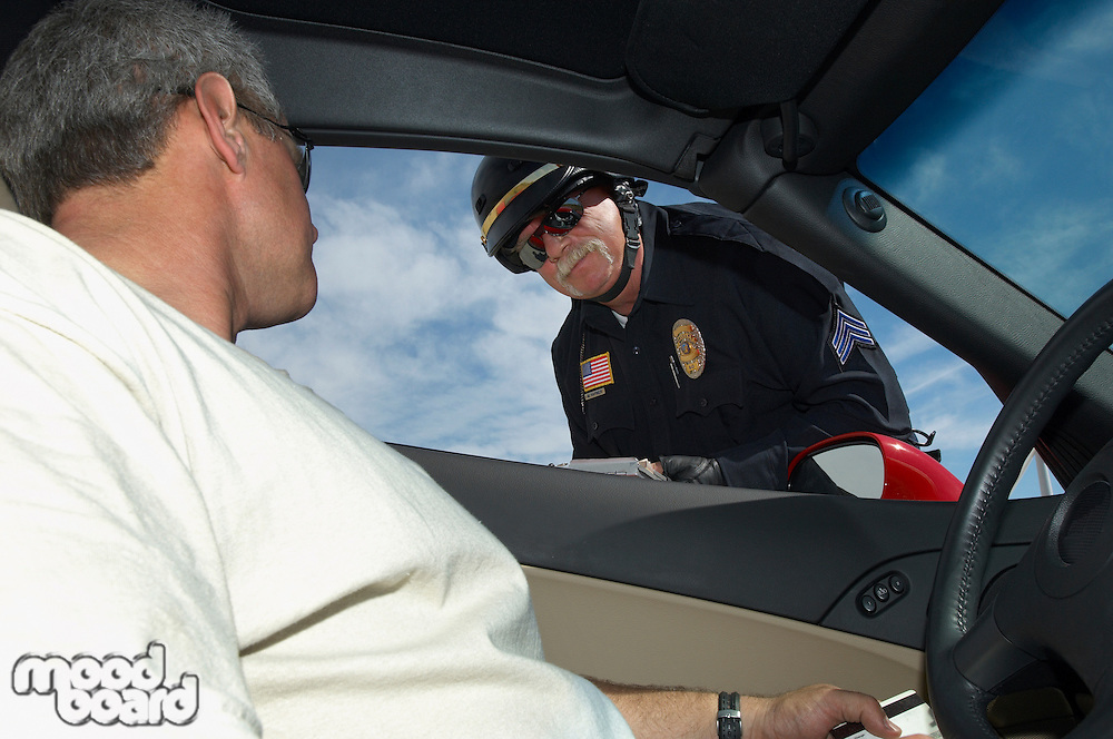 Police officer talking with driver, view from car