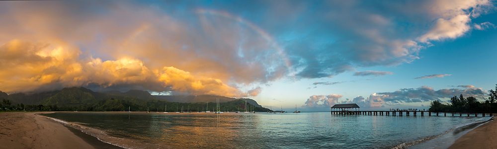 Panorama of storm clouds and rainbow over Hanalei Bay at sunrise, Kauai, Hawaii