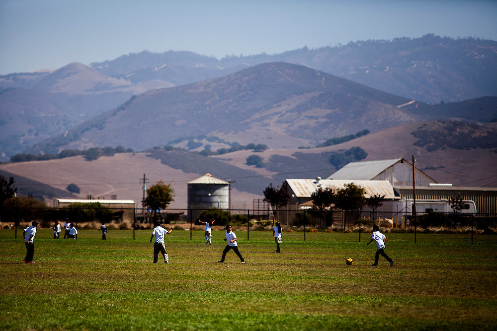 Students play in a field at Tiburcio Vasquez Elementary School with a view of a farm in the background in Salinas, California, U.S. on Monday September 8, 2014.