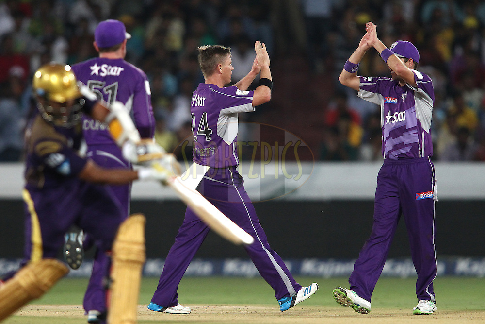 Xavier Doherty of the Hobart Hurricanes celebrates bowling Robin Uthappa of the Kolkata Knight Riders with Ben Laughlin of the Hobart Hurricanes during the first semi final match of the Oppo Champions League Twenty20 between the Kolkata Knight Riders and the Hobart Hurricanes held at the Rajiv Gandhi Cricket Stadium, Hyderabad, India on the 2nd October 2014<br /> <br /> Photo by:  Shaun Roy / Sportzpics/ CLT20<br /> <br /> <br /> Image use is subject to the terms and conditions as laid out by the BCCI/ CLT20.  The terms and conditions can be downloaded here:<br /> <br /> http://sportzpics.photoshelter.com/gallery/CLT20-Image-Terms-and-Conditions-2014/G0000IfNJn535VPU/C0000QhhKadWcjYs