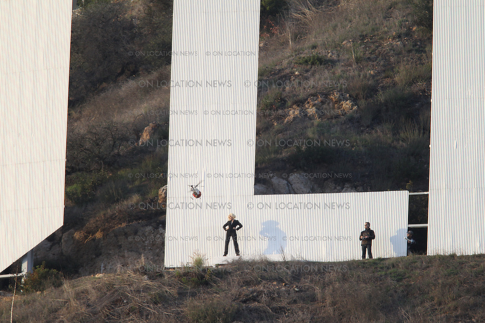 """Hollywood, CA. December 16th 2010 ***EXCLUSIVE*** Gwen Stafani films a commercial for L'Oréal at the """"L"""" of the famous Hollywood Sign. Gwen's son Kingston was brought on to the set for a visit. Gwen snapped and then posed for posed for photos with son Kingston at the Sign. Later a remote controlled helicopter camera filmed shots of Gwen posing at the Sign. Photos by Eric Ford/On Location News 818-613-3955 info@onlocationnews.com"""
