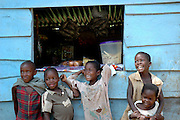 Children smile and laugh whilst standing outside the local village shop. Ssese Islands, Lake Victoria, Uganda, Africa.
