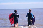 AJDN47 Two childen in black wet suits body boarding sea waiting for a wave