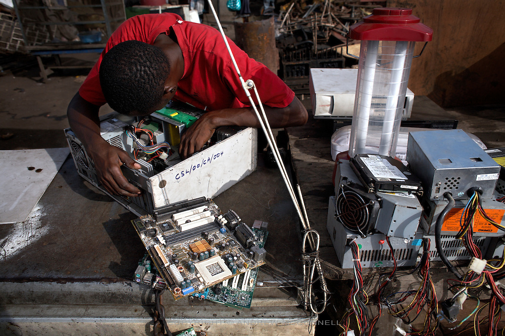 A man examines a hard drive at Agbogbloshie dump, in Accra, Ghana. Hard drives will be removed and sold for as little as $20, some will contain information that can be used by criminals.