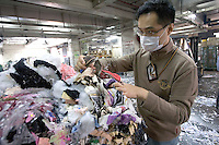 HONG  KONG, CHINA -  MARCH 22 : Hong Kong customs agent Terence Lau looks over destroyed counterfeit goods in Hong Kong, China on Thursday, March 22, 2007.  Among the many items that were destroyed were handbags, shoes and watches copied from many popular manufacturers such as Nike, Rolex, Gucci, Omega and Channel.  (Photo by David Paul Morris )