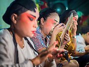 "14 MAY 2015 - BANGKOK, THAILAND:  Chinese opera performers put on their makeup before going on stage at the Pek Leng Keng Mangkorn Khiew Shrine in the Khlong Toey slum in Bangkok. Chinese opera was once very popular in Thailand, where it is called ""Ngiew."" It is usually performed in the Teochew language. Millions of Chinese emigrated to Thailand (then Siam) in the 18th and 19th centuries and brought their culture with them. Recently the popularity of ngiew has faded as people turn to performances of opera on DVD or movies. There are still as many 30 Chinese opera troupes left in Bangkok and its environs. They are especially busy during Chinese New Year and Chinese holiday when they travel from Chinese temple to Chinese temple performing on stages they put up in streets near the temple, sometimes sleeping on hammocks they sling under their stage. Most of the Chinese operas from Bangkok travel to Malaysia for Ghost Month, leaving just a few to perform in Bangkok.      PHOTO BY JACK KURTZ"