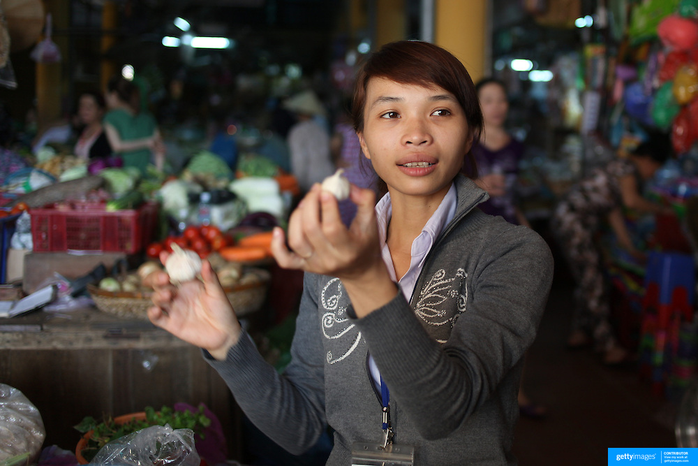 A Vietnamese tourist guide shows garlic for sale at the market in Hoi An, Vietnam. Hoi An is an ancient town and an exceptionally well-preserved example of a South-East Asian trading port dating from the 15th century. Hoi An is now a major tourist attraction because of its history. Hoi An, Vietnam. 5th March 2012. Photo Tim Clayton