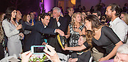 Sean Cummings returns Matthew McConaughey's shoes to Matthew's wife Camila Alves after paying $25,000 for them at auction at the New Orleans Film Society Gala at the home of Paul and Sara Costello on March 28, 2015; Photo: GeorgeLong.com