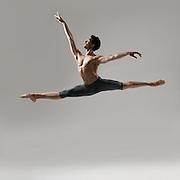 Classical male ballet dancer, Alexander Mays, jumping in the photo studio on a gray background. Photograph taken in New York City by photographer Rachel Neville.
