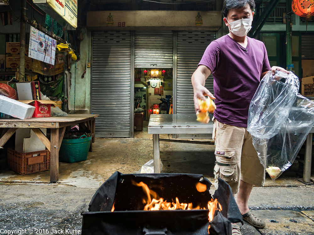 "07 FEBRUARY 2016 - BANGKOK, THAILAND: A man burns ""ghost money"" to make merit for Chinese New Year in Bangkok's Chinatown. Chinese New Year, also called Lunar New Year or Tet (in Vietnamese communities) starts Monday February 8. The coming year will be the ""Year of the Monkey."" Thailand has the largest overseas Chinese population in the world; about 14 percent of Thais are of Chinese ancestry and some Chinese holidays, especially Chinese New Year, are widely celebrated in Thailand.        PHOTO BY JACK KURTZ"