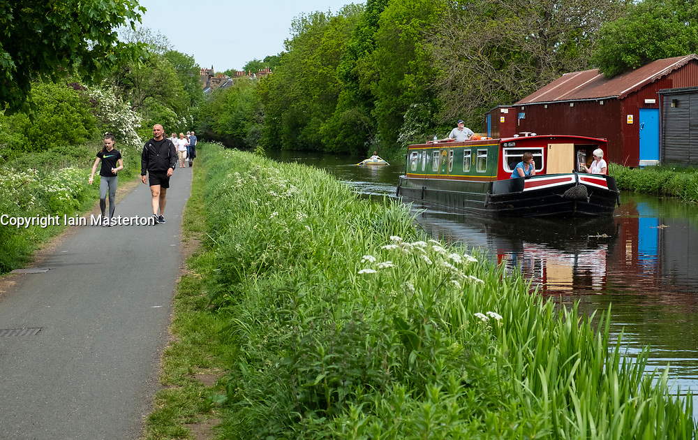 View of the Union Canal with narrowboat passing in Edinburgh, Scotland, United Kingdom