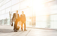 Mature businessmen walking while talking in the airport