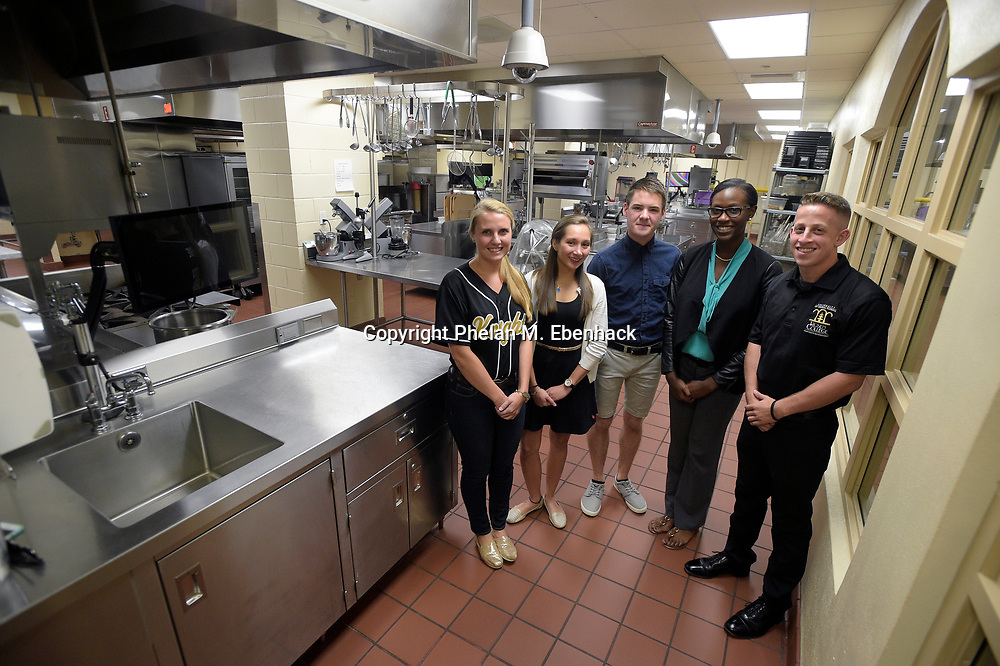 Hospitality management students Abbie Kellner, 20, left, Isabel Dugueyarza, 22, second from left, Ryan Lugo, 20, center, DiJai Dowling, 21, second from right, and Elliott Simon, 23, stand in a kitchen built specifically for classroom teaching in the Rosen College of Hospitality Management building at the University of Central Florida in Orlando, Fla., Tuesday, Aug. 25, 2015. (Photo by Phelan M. Ebenhack)